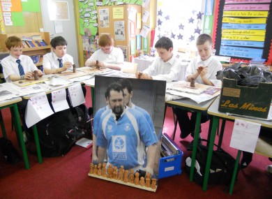 Schoolchildren contribute terracotta figurines to the Pitch for Shane project, in front of a portrait of the murdered rugby player.