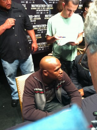 Money Mayweather at the top table, surrounded by journalists.