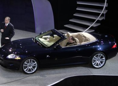 Lewis Booth, executive vice president of the Ford's Premier Auto Group of Europe stands next to a Jaguar XK convertible