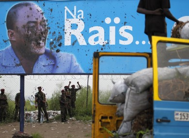 Presidential guardsmen stand under the stained campaign poster of Congolese President Joseph Kabila following clashes with supporters of opposition presidential candidate Etienne Tshisekedi at Kinshasa Airport.