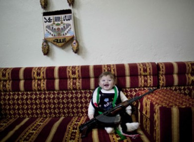 A six-month old poses with a machine gun owned by supporters of the Free Syrian Army. The photo was taken inside a house near Idlib in Syria.