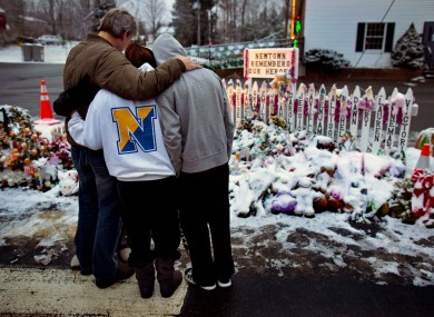 Members of the Rutter family of Sandy Hook, Conn., embrace early Christmas morning as they stand near memorials by the Sandy Hook firehouse in Newtown