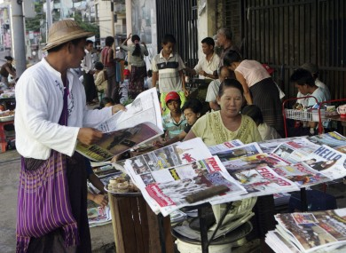 A man buys a weekly news journal at a roadside newspaper stand in Burma.