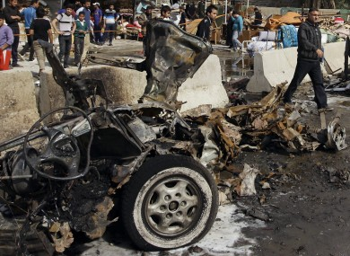 Iraqis inspect the scene of a car bomb attack in the Ameen neighborhood in eastern Baghdad, Iraq