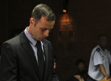 Olympic athlete Oscar Pistorius stands inside the court as a police officer looks on.