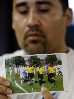 Jose Lopez points to an undated photo of Ricardo Portillo, centre, his brother-in-law.