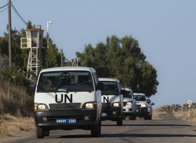 UN vehicles drive into a UN base near the Quneitra crossing between the Israeli-controlled Golan Heights and Syria