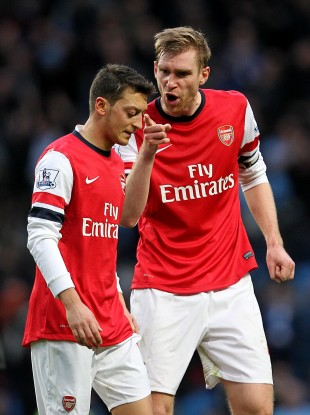 Arsenal's Per Mertesacker (right) shouts at team-mate Mesut Ozil after the final whistle.
