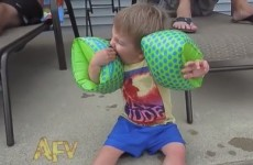 Cute kid learns it's very difficult to eat with arm bands on