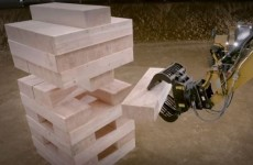Guys play massive game of Jenga using heavy machinery